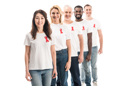 gruppo sorridente di persone in magliette bianche vuote in piedi in fila con nastri rossi di consapevolezza dell'AIDS isolati su bianco