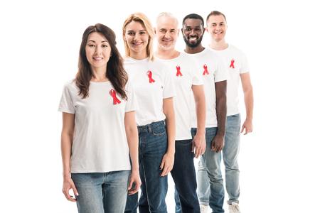 Sonriente grupo de personas en camisetas blancas en blanco de pie en fila con cintas rojas de concienciación sobre el sida aislado en blanco