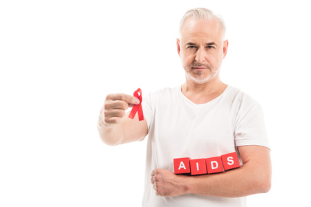 mature man in blank white t-shirt with aids awareness red ribbon and blocks with AIDS lettering isolated on white