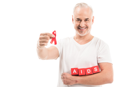 happy mature man in blank white t-shirt with aids awareness red ribbon and blocks with AIDS lettering isolated on white Stock Photo