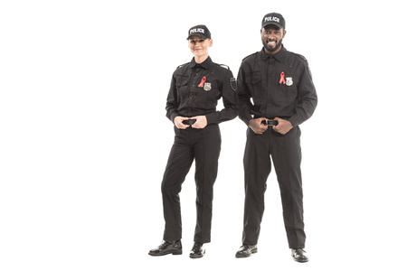 confident young police officers with aids awareness red ribbons looking at camera isolated on white