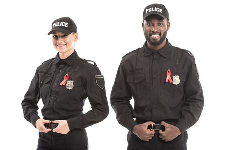 confident multiethnic police officers with aids awareness red ribbons looking at camera isolated on white Stock Photo