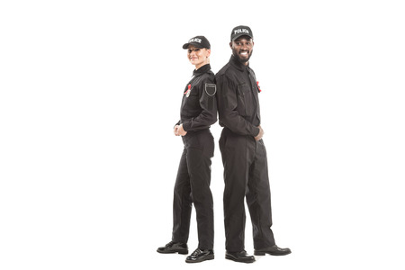 smiling police officers with aids awareness red ribbons looking at camera while standing back to back isolated on white