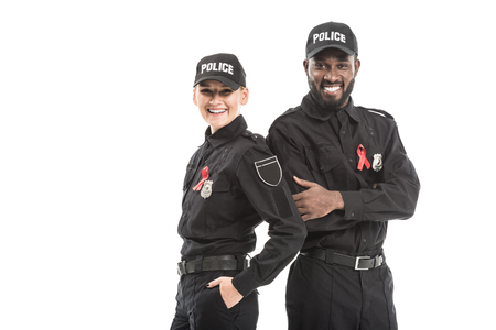 confident police officers with aids awareness red ribbons looking at camera isolated on white
