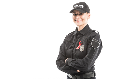 happy female police officer with aids awareness red ribbon looking at camera with crossed arms isolated on white
