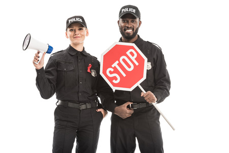 smiling police officers with stop road sign and megaphone looking at camera isolated on white, aids awareness concept