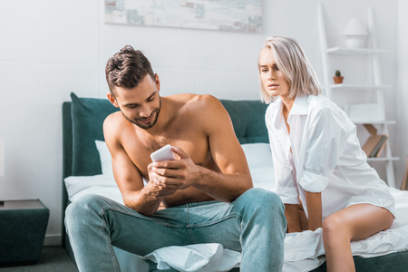 jealousy young man using smartphone of his girlfriend while she sitting on background in bedroom
