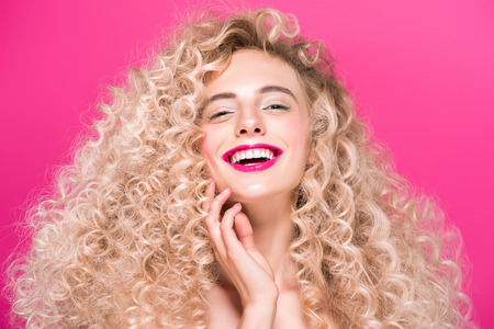 attractive naked girl with long curly hair smiling at camera isolated on pink Banque d'images - 110309035