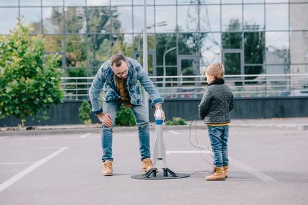 padre e hijo jugando con cohete modelo juntos Foto de archivo