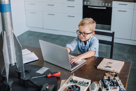 high angle view of boy using laptop at table with rocket model in kitchen on weekend Stock Photo