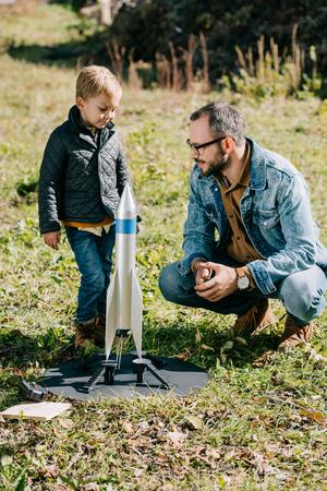 feliz padre y lindo hijo jugando con el modelo de cohete al aire libre