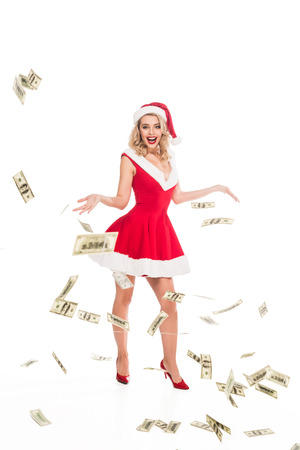 happy santa girl in christmas hat throwing out cash money isolated on white
