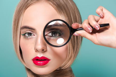 beautiful young woman holding magnifying glass and looking at camera isolated on blue Imagens