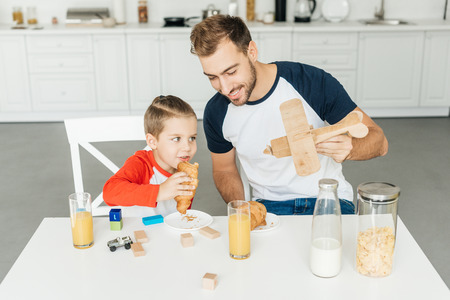 handsome young father and son playing with toy plane while having breakfast together at home