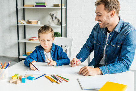 happy young father drawing with adorable little son at home