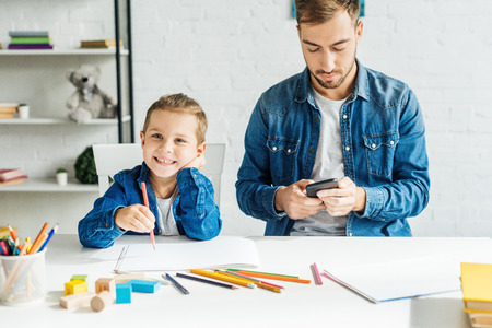 handsome young father using smartphone while son drawing at home