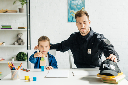 handsome young father in police uniform and son playing together at home Reklamní fotografie