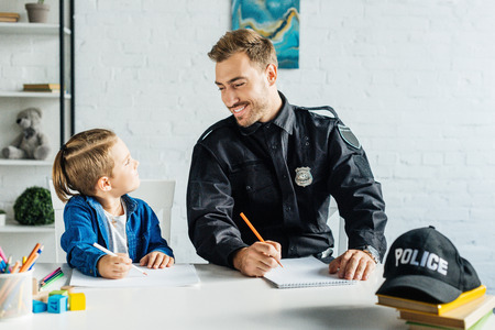 happy young father in police uniform and son drawing together at home