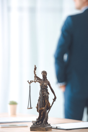close-up view of lady justice statue and lawyer standing behind Stock Photo