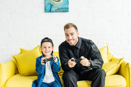 happy young father in police uniform and son playing video game while sitting on yellow couch at home