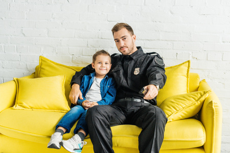 young father in police uniform watching tv with son while sitting on yellow couch at home Stock Photo