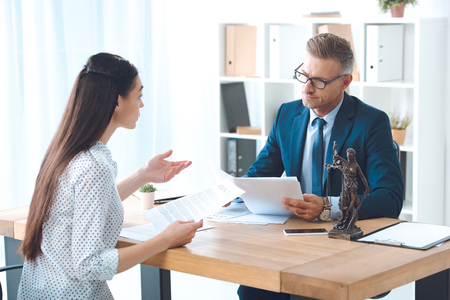 lawyer and client holding papers and discussing contract in office