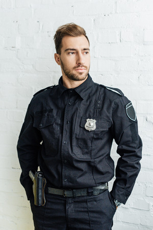 portrait of handsome young policeman in front of white brick wall
