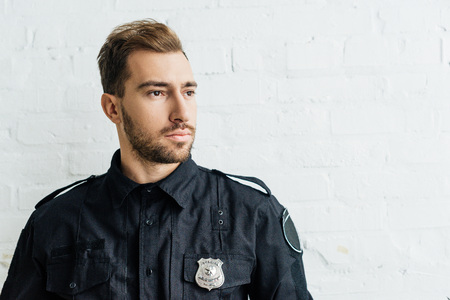 portrait of thoughtful young policeman in front of white brick wall