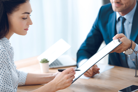 cropped shot of lawyer holding clipboard and young woman signing document Imagens - 110337163