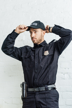 handsome young policeman putting on cap in front of white brick wall Stockfoto