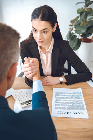 businesspeople arm wrestling at workplace in office