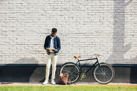 african american freelancer reading documents and standing near bicycle at white brick wall Stock Photo