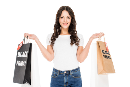 smiling girl holding shopping bags with black friday sale signs isolated on white Stock Photo
