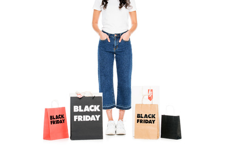 cropped view of woman posing at shopping bags with black friday sale signs isolated on white