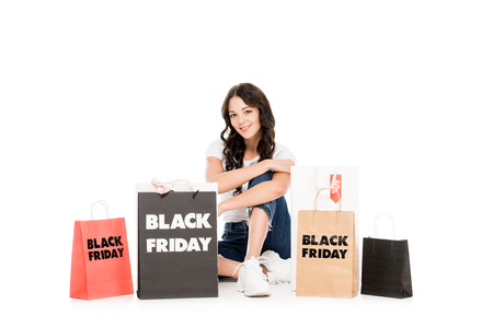smiling girl posing at shopping bags with black friday sale signs isolated on white