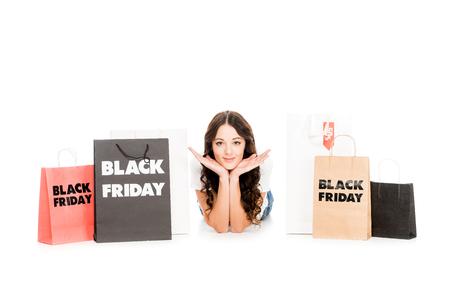 happy stylish shopaholic lying at shopping bags with black friday symbols isolated on white Stock Photo