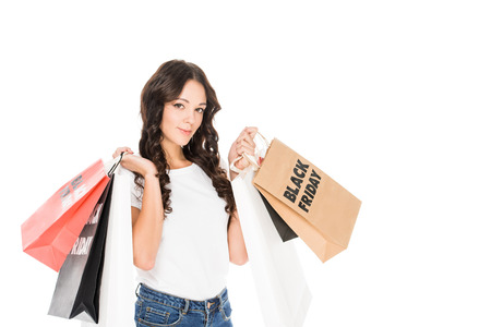 attractive girl holding shopping bags with black friday sale signs isolated on white