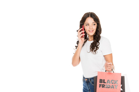 beautiful girl talking on smartphone and holding shopping bags with black friday sign isolated on white Stock Photo