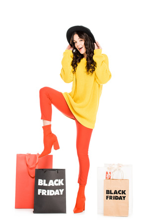 excited stylish girl posing near shopping bags on black friday sale, isolated on white Stockfoto