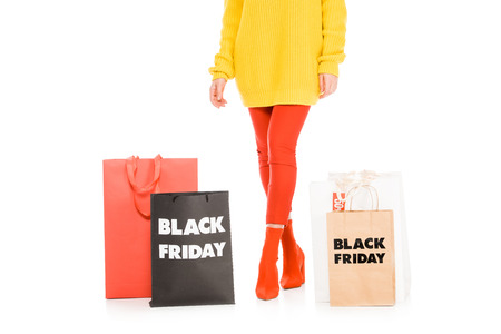 cropped view of stylish girl posing near shopping bags on black friday sale, isolated on white