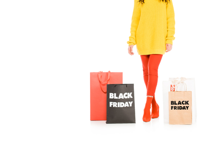 cropped view of customer posing near shopping bags on black friday sale, isolated on white