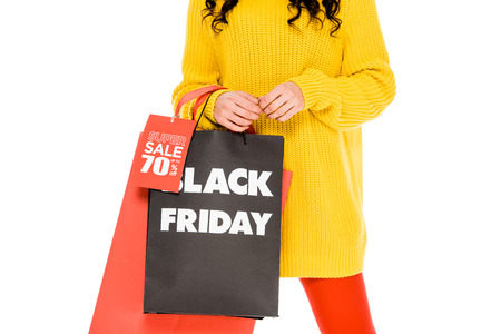 cropped view of girl holding shopping bags on black friday sale, isolated on white Stockfoto