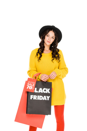 fashionable young woman in hat holding shopping bags on black friday sale, isolated on white