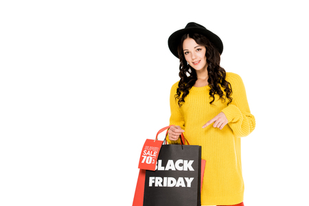attractive customer pointing at shopping bags on black friday sale, isolated on white
