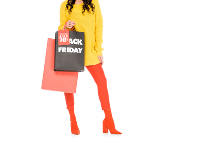 cropped view of stylish girl holding shopping bags on black friday sale, isolated on white Stockfoto