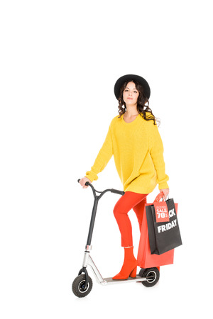 beautiful young woman riding scooter with shopping bags for black friday isolated on white