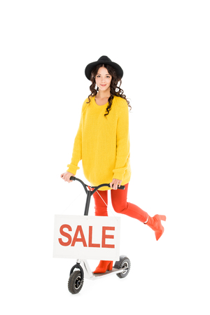 beautiful stylish girl riding scooter with sale sign isolated on white