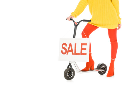 cropped view of stylish girl riding scooter with sale sign isolated on white