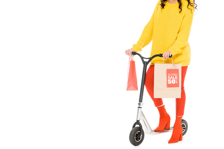 cropped view of customer riding scooter with shopping bags isolated on white