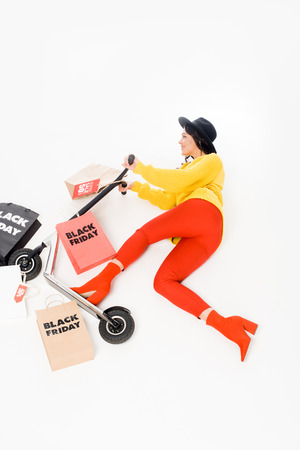 top view of female customer riding scooter with shopping bags for black friday isolated on white